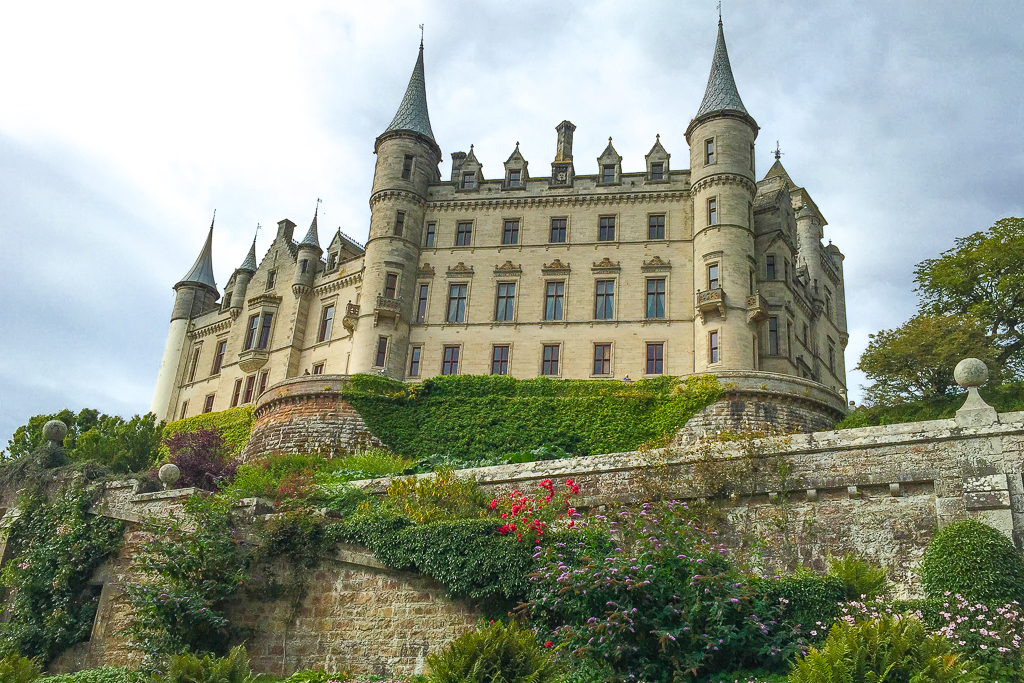 Image of Dunrobin Castle in Golspie, Scottish Highlands. Looking up at one side of the large castle, with turrets and many windows. Just a glimpse of the well manicured gardens in the foreground.