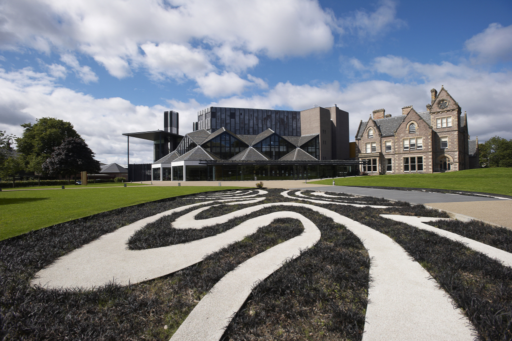 Image of the exterior of Eden Court Theatre and Cinema. Image of a black and white graphic landscape flower bed in front of the Bishop's Palace building and the modern Eden Court building.