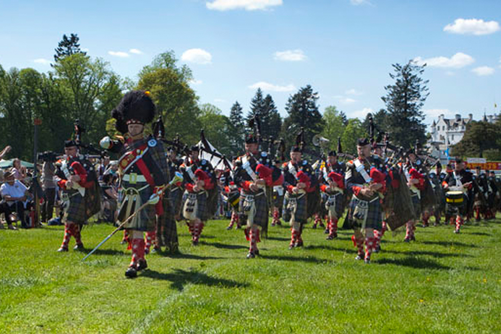 Image of a Scottish bagpipe band at Scottish Highland games. Dressed in full military dress, with a Pipe Major, bagpipe players and drummers.
