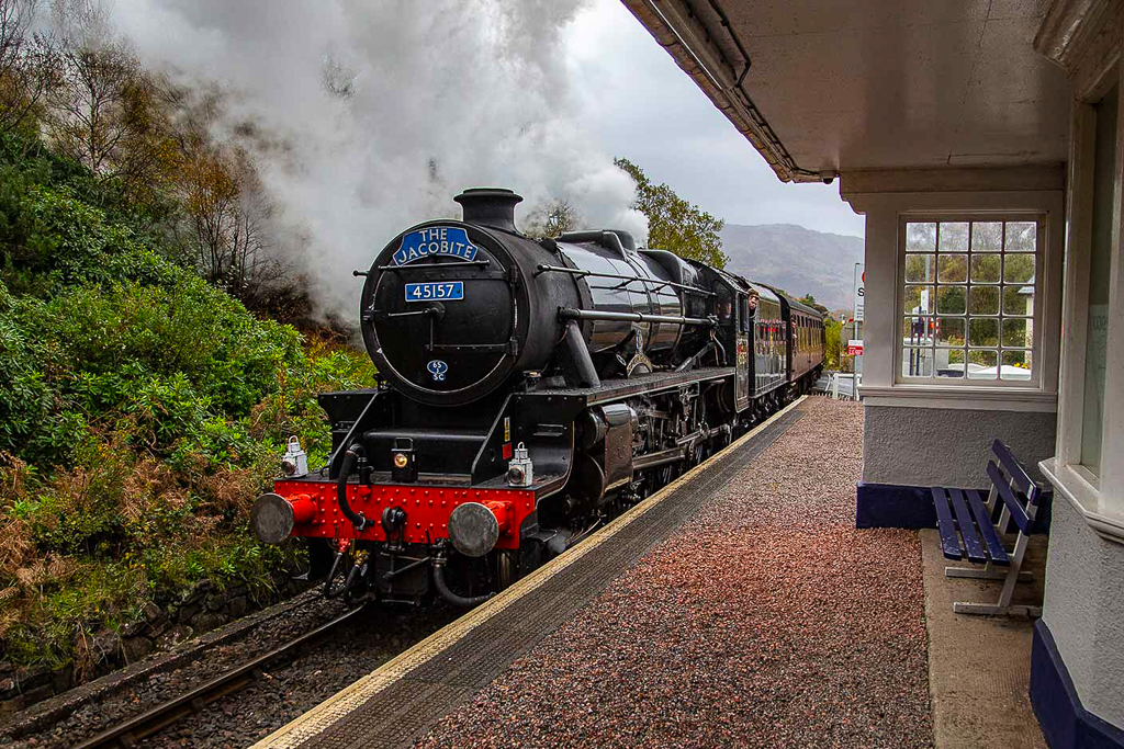 Photograph of The Jacobite steam train, standing at an old fashioned railway station.