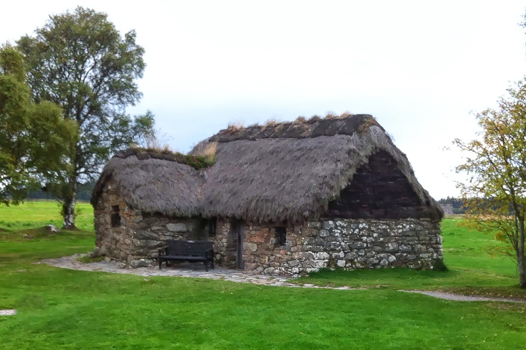 An image of Leanach Cottage on Culloden Moor. It's a small stone built cottage from the early 18th century, with very small windows and a thatched roof.