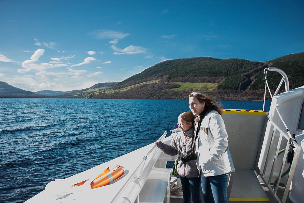 Image of Loch Ness, taken from aboard a Jacobite Tours boat, sailing on Loch Ness with a woman and a young child looking at the Loch. Hills in the background, the water is still and blue.
