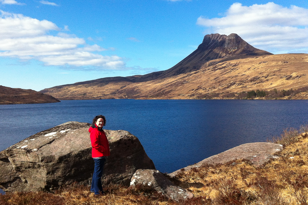 Photograph of Susan standing on the shores of a Loch with Stac Polliaidh mountain in the background. Dark blue water of the loch, contrasts with Susan's bright red jacket and the vibrant cobalt blue sky.