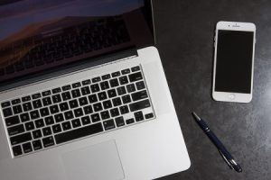 Close up image of Apple Mac laptop, smartphone and a pen