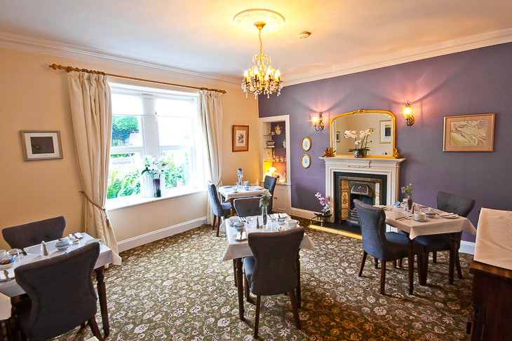 Image of the dining room at The Ness Guest House, B&B Inverness. Showing a Victorian style room with tables and chairs and a fireplace.