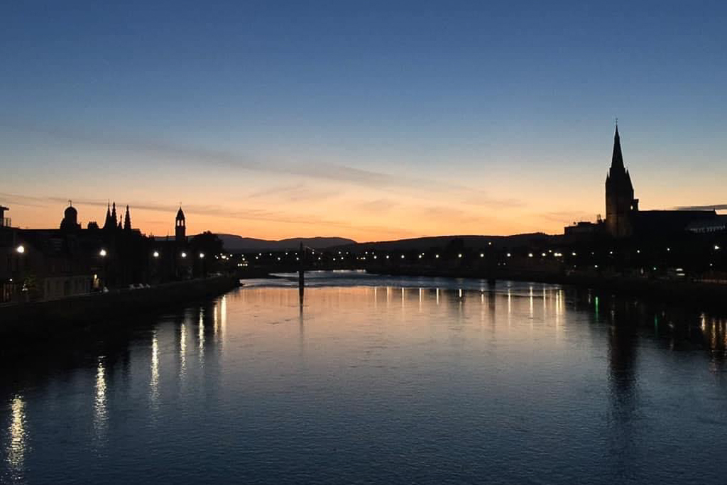 An image of The River Ness at Dusk with the spires of Inverness churches on the skyline. Beautiful reflections of the street lights on the calm water.