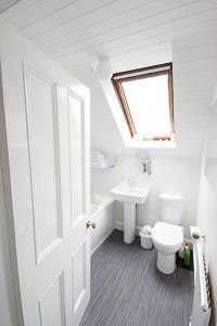Picture of Double Room 2 Bathroom with Shower over the bath at The Ness Guest House B and B in Inverness, image shows a toilet, wash hand basin and corner of the bath.