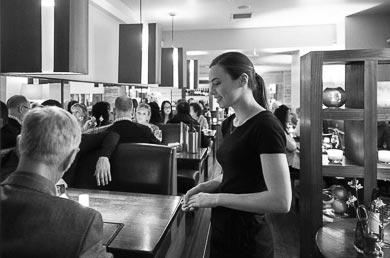 A black and white photograph of the interior of Rocpool restaurant in Inverness city centre. It shows a waitress serving a table, in the background are several more booths and tables, full of customers.