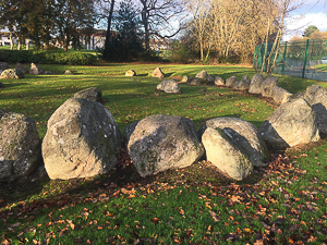 Large stones in a circle, on grassy field, with trees in background