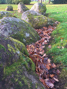 Close up of large stones in a stone circle, with a river of leaves